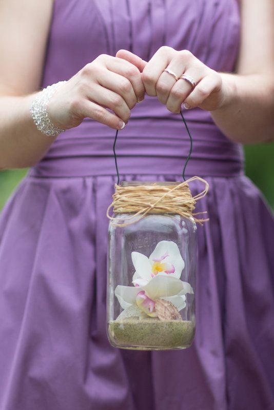 bridesmaid bouquet alternative. flowers seashells and sand in mason jar lantern. beach theme wedding