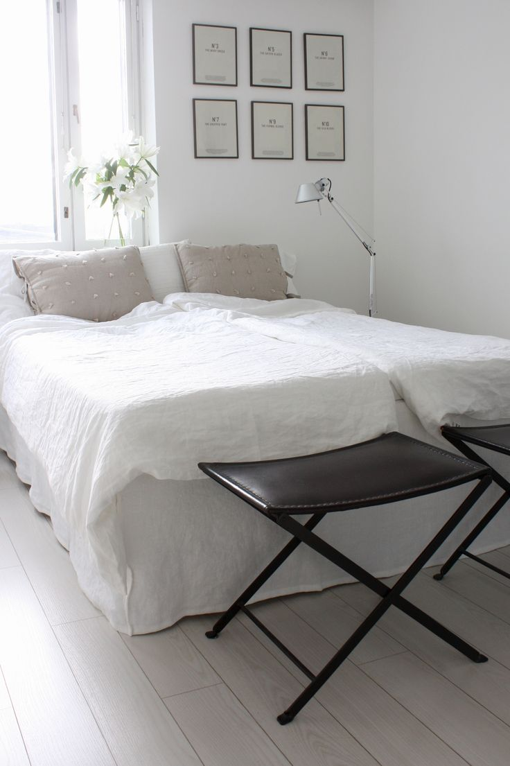 Homevialaura | White bedroom with Artemide Tolomeo lamps, linen sheets, Bemz Loose Fit Urban bed skirt, gallery wall, white lilies and Kartell Jolly tables