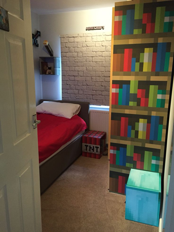 Minecraft themed bedroom. Bookcase is customised vinyl attached to the side of his wardrobe - from www.brokenpencil.co.uk. Blackout blind from Dunelm. Bedding is white linen with plain red duvet cover from Argos. Stone wall mounted box and TNT are customised IKEA boxes again from www.brokenpencil.co.uk. Official wall mounted Minecraft light from Firebox. Complete with a little 'Ellie' as homage to Dan TDM.