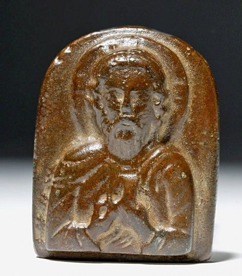 Byzantine Empire, ca. 10th to 12th century CE. A near-miniature, tombstone-shaped, solid-cast bronze icon with a bas-relief image of St. Nicholas, The Wonderworker, holding the Gospel in his left hand and pointing to his chin with his right, with a cross on the verso. Notice the remarkable technique of this piece, in particular the elegant delineations of St. Nicholas's wavy hair and the folds of his cascading robe.