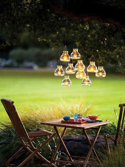 Love the little lanterns hanging over a table outdoors.
