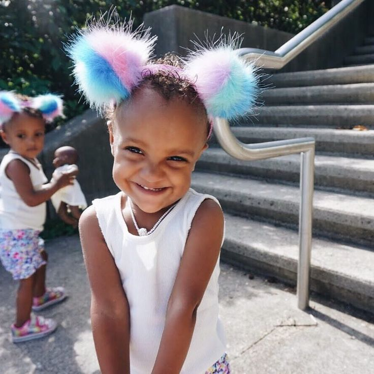 Identical twins wearing their Claires Pom Pom headbands and looking adorable
