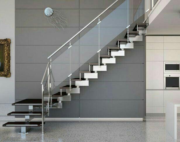 Escada com degraus estilo inox e corrimão de vidro com barra inox.
