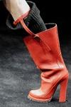 Necesitarás unas katiuskas. Prada diseña un modelo de caña ancha con tira liguero y calcetín pescador de punto con vuelta.