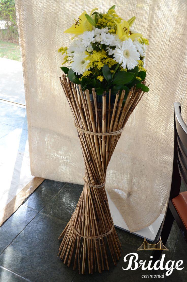 Arranjos em suportes de bambu neste casamento rústico