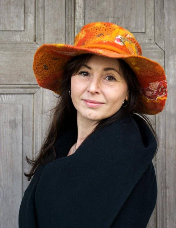 Unique and elegant orange felted hat in bohemian style with wide floppy brim. This stylish hat is made nuno felting technique with best quality merino wool and pieces of decorative silk fabric, gold shiny mesh, silk fibers and wool curls. Decorated with long orange felted wool strap. Light,