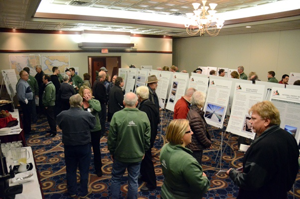 Green-jacketed Kinder Morgan representatives at an open house Tuesday speak with attendees about the proposed twinning of the Trans Mountain pipeline.
