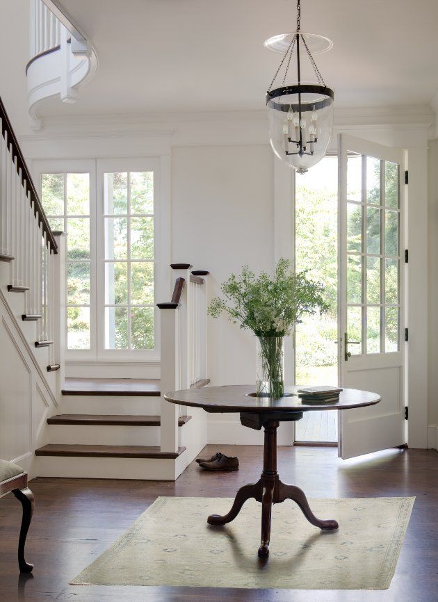 Even if your foyer is on a smaller scale  you can incorporate a sense of the Hamptons style using dark flooring and white millwork. And don't forget a centrally placed table for drama and scale