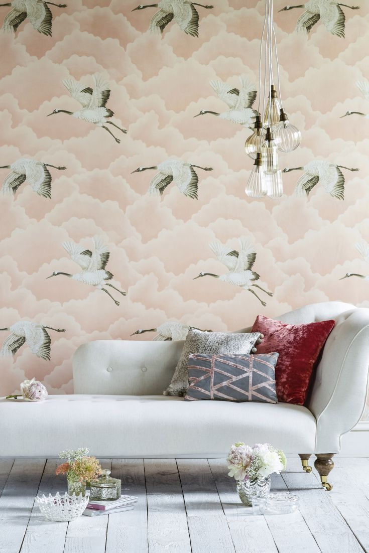 This pretty blush pink wallpaper pattern features cranes flying through clouds.