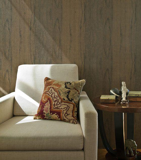 Ambientes de uso comum pedem uma decoração mais aconchegante e neutra, como a decoração da foto, com papel de parede com imitação de madeira em tons fortes e detalhes sutis, contrastando com o sofá em tons claros, criando uma sensação de sofisticação e sobriedade à sala.