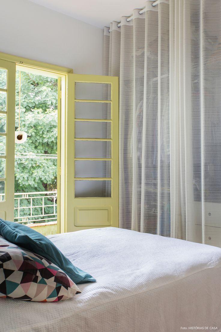 Nesse quarto de casal usou-se a cortina de ponta a ponta da parede para esconder as prateleiras com roupas e televisão.