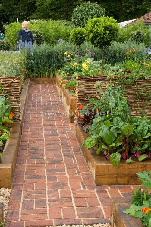 Vegetable garden with brick pathway and girl scarecrow, wide view