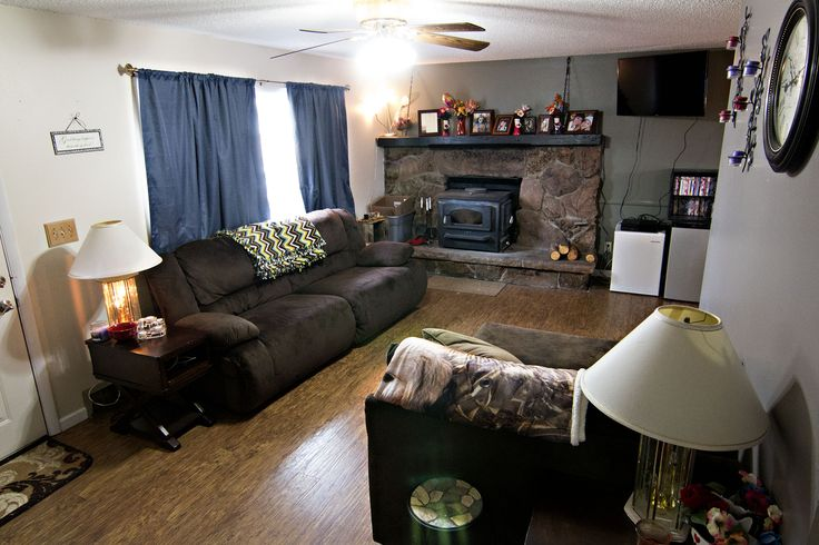 The living room of 4000 Force Rd Gillette, WY features cool tones and a rock accented fireplace. Sit back and relax! Call Team Properties Group for your showing 307.685.8177