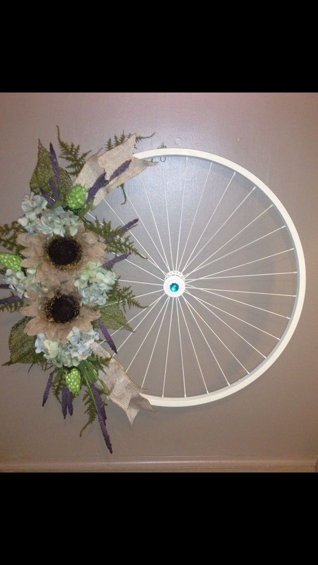 Old bike wheel, spray paint, a glue gun, and 15 bucks worth of flowers!! So simple to make!