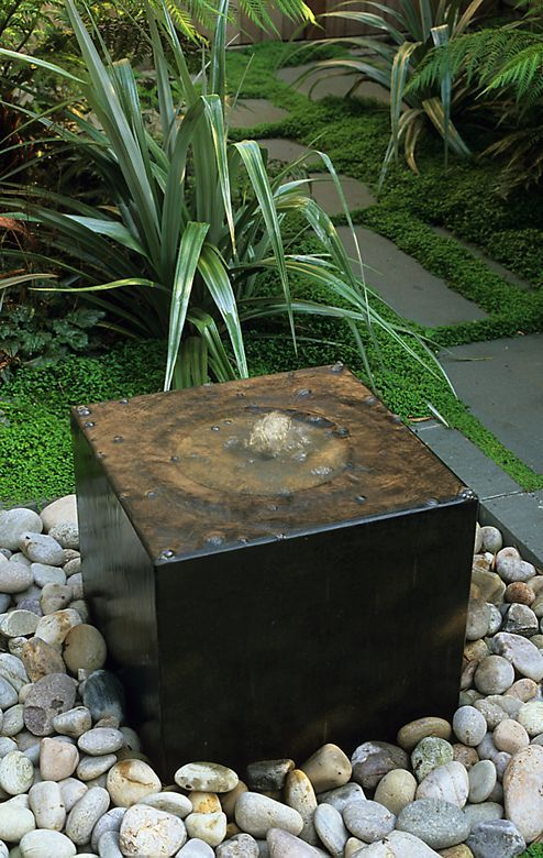 Water features do not have to be massive in size. One like this usually has a water reserve like a 5 gallon bucket placed under the ground with a recycle pump. The rocks cover the reservoir and allow the water to flow back to the pump.