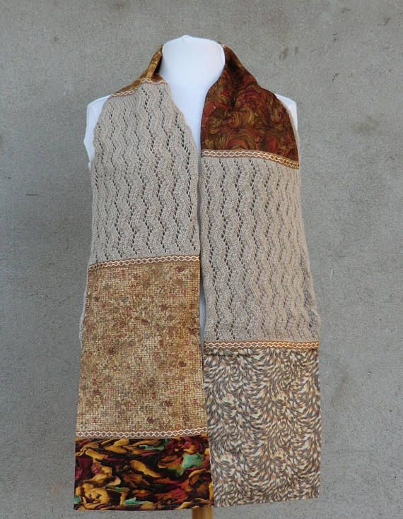 Écharpe / Étole Fantaisie Une belle idée de cadeau original et unique, à offrir ou à soffrir..  Création personnelle Modèle unique et original Alliant le tissu, la laine et le galon de passementerie Longueur 185cm Largeur 23cm Modèle réalisé à la main dans de très beaux coloris de tons marron et beige Lécharpe est constituée en patchwork de 5 tissus à motifs différents Tissu 100% coton Les rectangles en laine 100% acrylique Coloris beige Tricotés à la main en point fantaisie de Zig Zag a...
