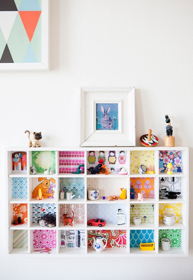 DIY kids room shelving splash of color - transform plain kids shelves with scrapbooking paper, fabric scraps, old birthday cards, anything to give a terrific backdrop for shelving.