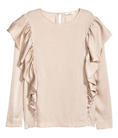 Lichtbeige. Een blouse van zacht satijn met lange mouwen. De blouse heeft volants op het voor- en het achterpand en een splitje achter met een knoop in de