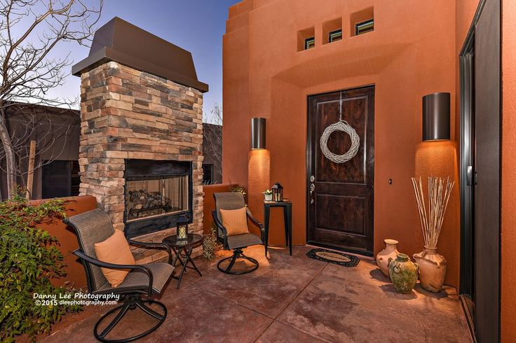 Southwestern Patio with Antique Bronze Cylinder 1 Light Outdoor Wall Sconce, Woodard Fremont Sling Highback Swivel Rocker