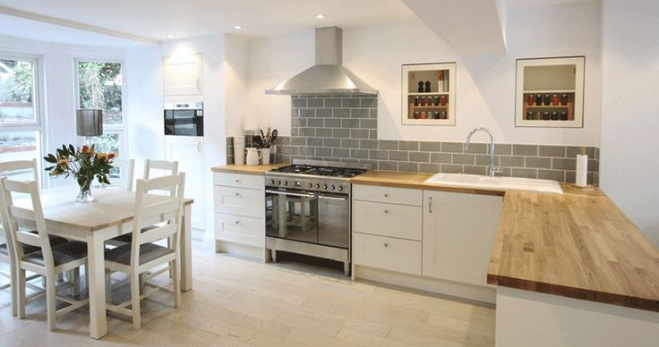 I love the clean white walls and simple cupboards with the grey tiles and chunky wooden top