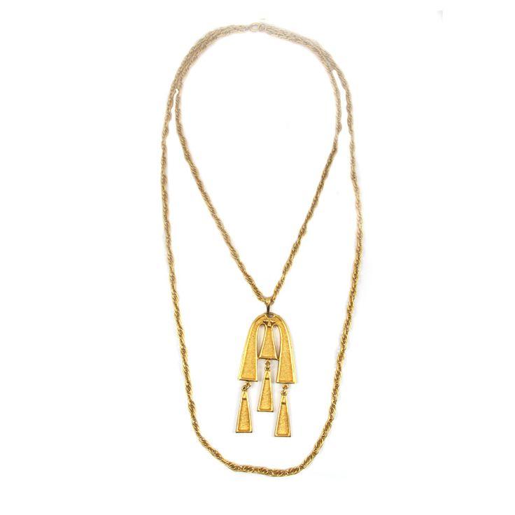 Questo girocollo vintage della Trifari è stato fatto negli anni 1960. La collana è a doppio filo (catena) con pendente geometrico in metallo dorato. Il gioiello è di colore oro. L'ornamento si chiude con un anello a molla. Condizione perfetta