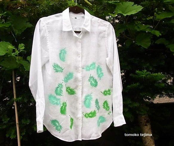 布用の耐水性の絵の具を使って服に直接絵を描いています。白いリネンシャツに表裏にみどりの羽を舞うように描いています。表はやさしい新緑のような緑を中心に、裏は黄緑... ハンドメイド、手作り、手仕事品の通販・販売・購入ならCreema。