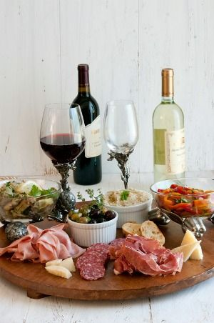 Wine & Antipasto Platter: Arrange the salami, mortadella, prosciutto, and Parmesan cheese on a large platter. Serve the crostini, artichokes, olives, white bean puree, and peppers along side in separate bowls.