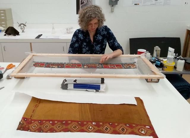 Associate Conservator Fran Baas with the Dallas Museum of Art works to conserve Andean textiles.