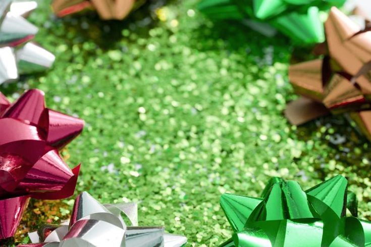 Green glitter background with bow frame of metallic shiny spiky ribbon bows for a festive party celebration or Christmas greeting - free stock photo from www.freeimages.co.uk