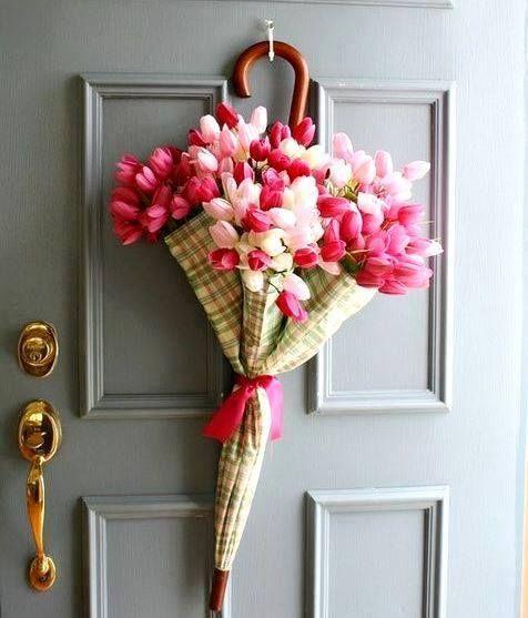 Sombrinha enfeitada com flores dependurada na porta de entrada da casa.