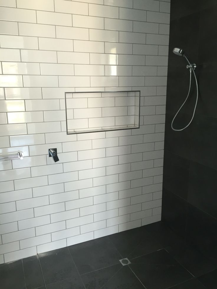 Classic look Ensuite. 100x200 metro tiles with a grey grout as the feature wall among the 450x450 charcoal tiles.