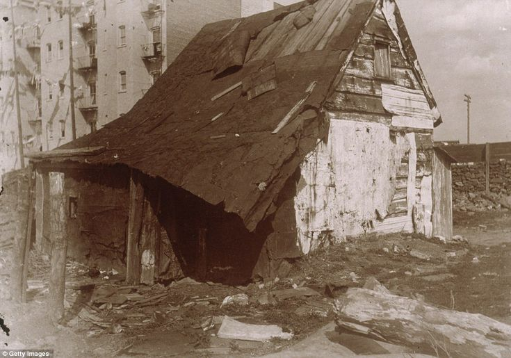 Shanty town: A dilapidated wooden shack sits in an empty lot surrounded by tenement buildings in 1896