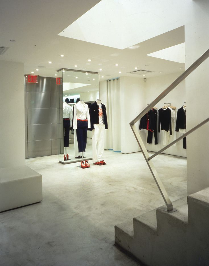 This space is characterized by the use of light tones and the materials like concrete, metal and mirrors. These choices wants valorize the clothes insade the room. #DG #dolce #gabbana #newyork #boutique #fashion #design #contemporary #interior #design #scale #white #railing #concrete #floor