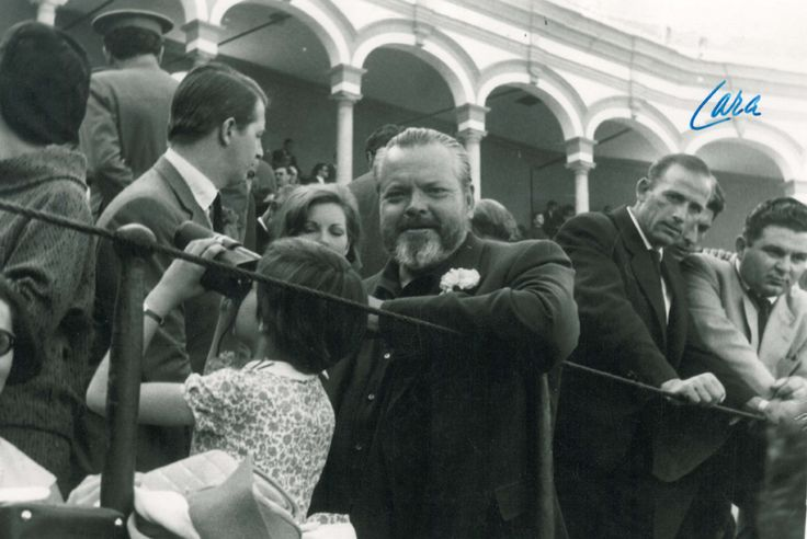 Beatrice Welles looks through binoculars into the crowd as her father, Orson Welles peers directly into the camera at an annual bullfight held at the Feria de Sevilla in Spain during April 1964 (Agencia Gráfica Prensa Lara, Madrid). Image courtesy the University of Michigan Library, Special Collections.