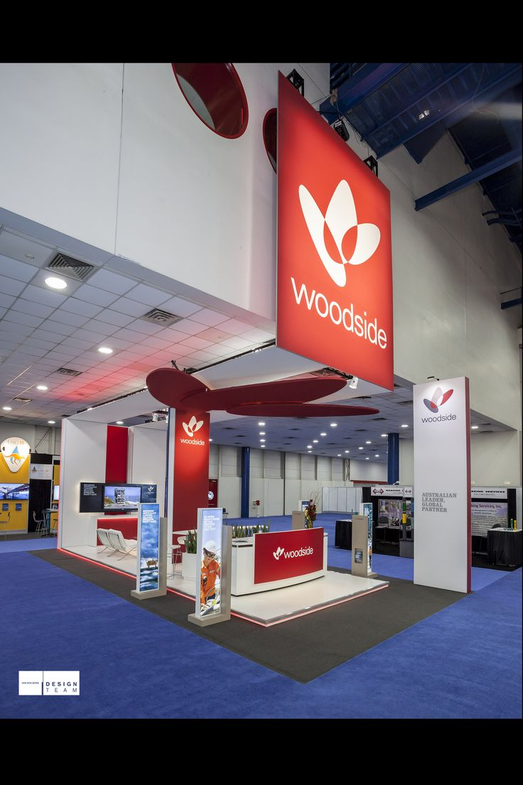 WOODSIDE @ LNG Woodside has been a long term client of Designteam so they were comfortable using our services to design, fabricate and install their stand at LNG 17 in Houston Texas. The stand is located in a difficult position tucked away under a low ceiling in an enormous hall. Our solution is to wrap around the building's bulkhead with huge signage which can and is seen from afar. It is an outstanding success, with high recognition, on budget and completed early.