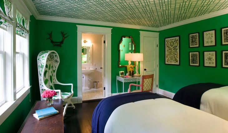 David Cafiero designed kelly green bedroom with white, navy, and a classic chair.