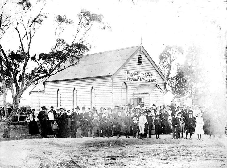 A group in front of the Horsham Church of Christ. A sign on the church reads: 'Harward is coming. See posters for protracted meeting.' c1905.