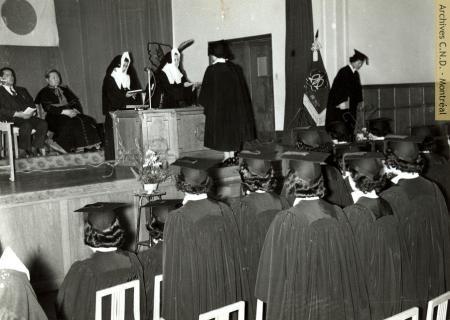 Sœur Sainte-Régina (Marcella MacGillivray) donne les parchemins aux finissants lors de la première remise de diplômes au Sakura no Seibo College (Collège junior Notre-Dame-des-Cerisiers), Fukushima, Japon, 8 mars 1957. Archives Congrégation de Notre-Dame - Montréal.