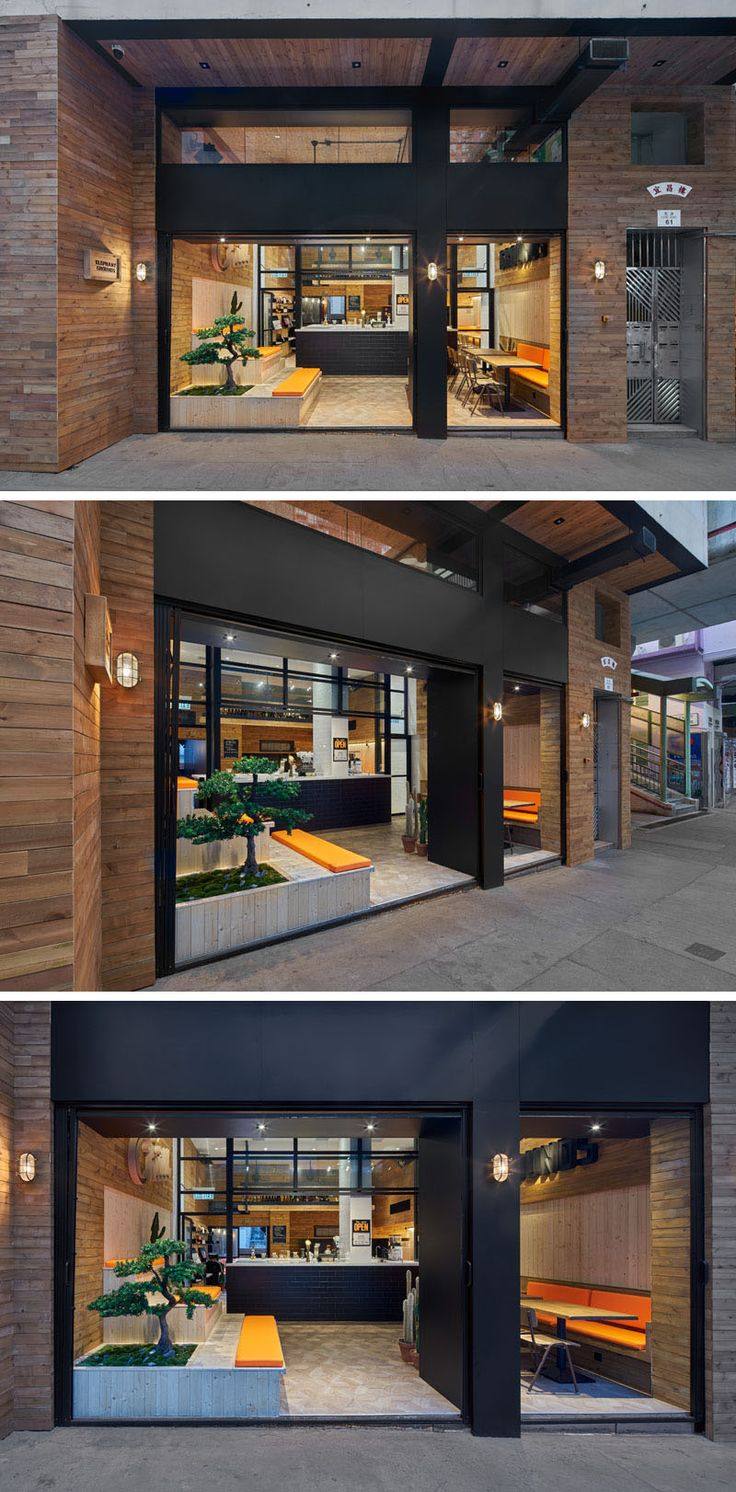 The facade of this modern coffee shop is open to the street and defined by a dual black door frame surrounded by wood.