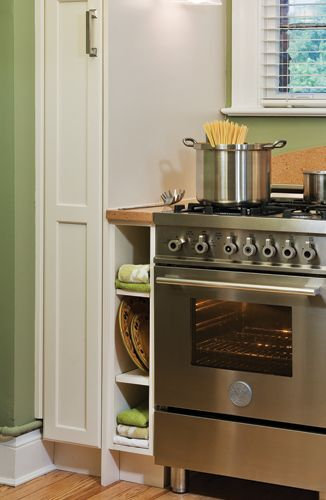 The stove is flanked by narrow cubbies that take advantage of every inch of space