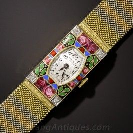 Here is simply one of the coolest and most distinctive Art Deco era wrist watches we've had the good fortune to acquire. By the Swiss watchmaker, E. Gubelin, the tonneau shape dial is elaborately ornamented with a multi-color floral design, punctuated on each corner with a small diamond. The supple mesh bracelet is composed of tri-color 18K yellow, rose and white gold stripes. The hand engraved buckle clasp matches the sides of the timepiece. A stunning and sophisticated timepiece - circa…