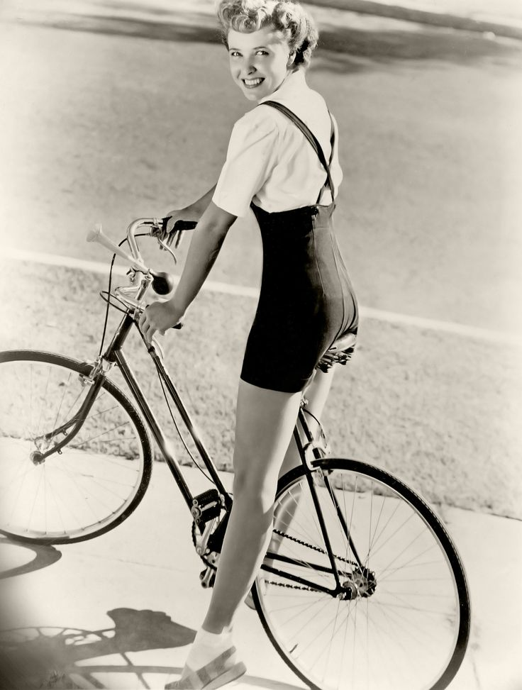 Actress Laraine Day looking cute as a button in her summery shortalls/suspender shorts and blouse as she zips about on a bike.