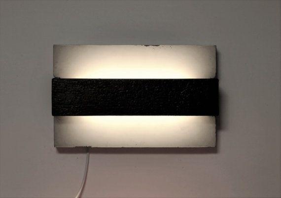 Lampada da muro in cemento, con un inserto di legno bruciato che conferisce un effetto molto particolare. Il legno bruciato è trattato in maniera di