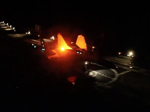 Naval fighter MiG-29K night landing and taxiing to aircraft carrier