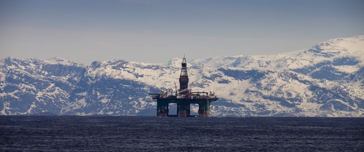 Arctic oil rig in stark contrast with mountains