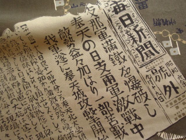 Kimono fabric reporting on the Manchurian Incident. The Mainichi Shimbun newspaper cutting is dated 19th. Sept. 1931. It states that on the 18th. Sept. at 11:00pm, the Chinese exploded a bomb on the tracks of the South Manchurian Railway. This was just one of a series of events that would lead to the Japanese invasion of Manchuria.