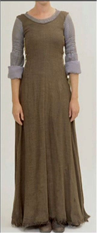 Eowyn's Refugee Outfit: It has a rounded neck with the neckline gathering slightly under the neck binding. There is gold thread around the neck binding as well. The sleeves are lined in light blue. Blue cord binds the upper arms. The skirt of this costume is split in two up the front. The brown jumper is sleeveless, has brown piping around the neck, a seam up the back, no seam up the front . The side is scalloped and laced. She wears brown leggings underneath and the travel boots.
