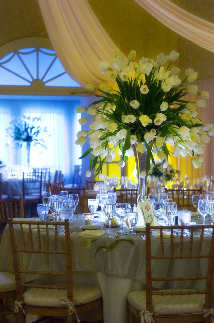 Merion Cricket Club in Haverford, PA.  A mass of 150 French tulips decorated the bridal table. Hand painted linens and table numbers were painted by Alix Jacobs of Haverford. Draping in the ballroom was done by Jeff Faust.  Nancy Saam Flowers Photo Credit: Joanne Bening
