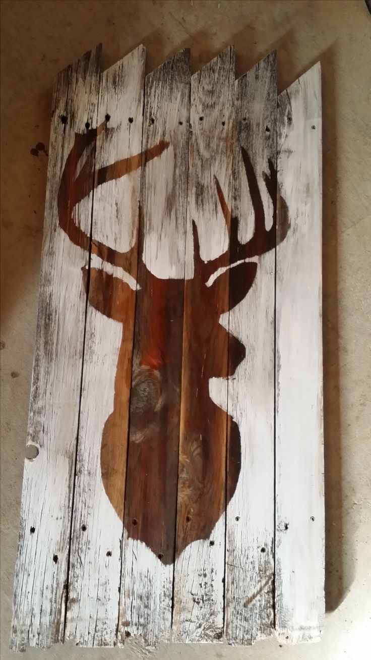 Old picket fence, stained then whitewashed over a deer head stencil.  Sanded to let some of the old come through.