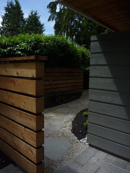 The freestanding wall of unstained lumber acts as a screen to hide the pathway from passersby.